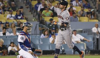 Houston Astros' Josh Reddick (22) crosses home plate in front of Los Angeles Dodgers catcher Austin Barnes (15) after a three-run home run during the eighth inning of a baseball game Saturday, Aug. 4, 2018, in Los Angeles. (AP Photo/John McCoy)