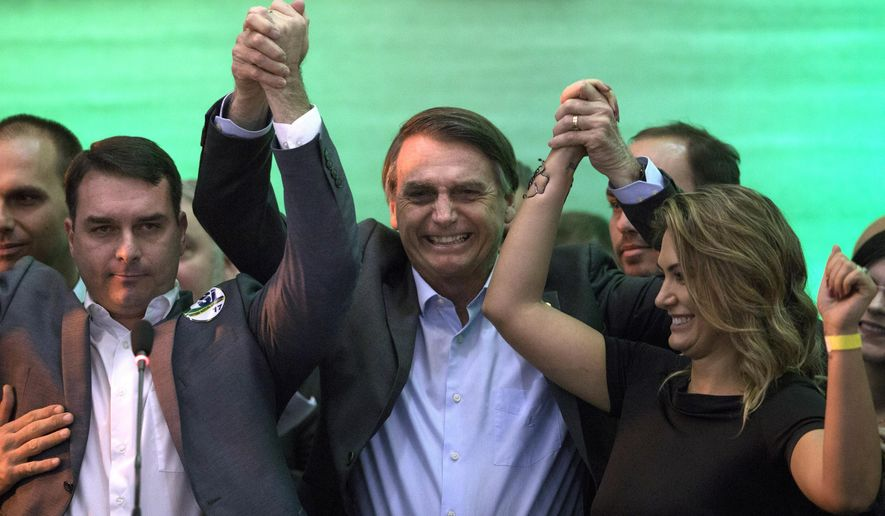 FILE - In this July 22, 2018 file photo, Brazil's presidential candidate Jair Bolsonaro, center, holds hands with his wife Michelle and son Flavio before supporters during the National Social Liberal Party convention where he accepted the party's nomination in Rio de Janeiro, Brazil. The far-right presidential candidate announced on Sunday, Aug. 5, 2018 that he has picked Army Reserve General Hamilton Mourao as his running mate for Brazil's upcoming general elections in October. (AP Photo/Leo Correa, File)