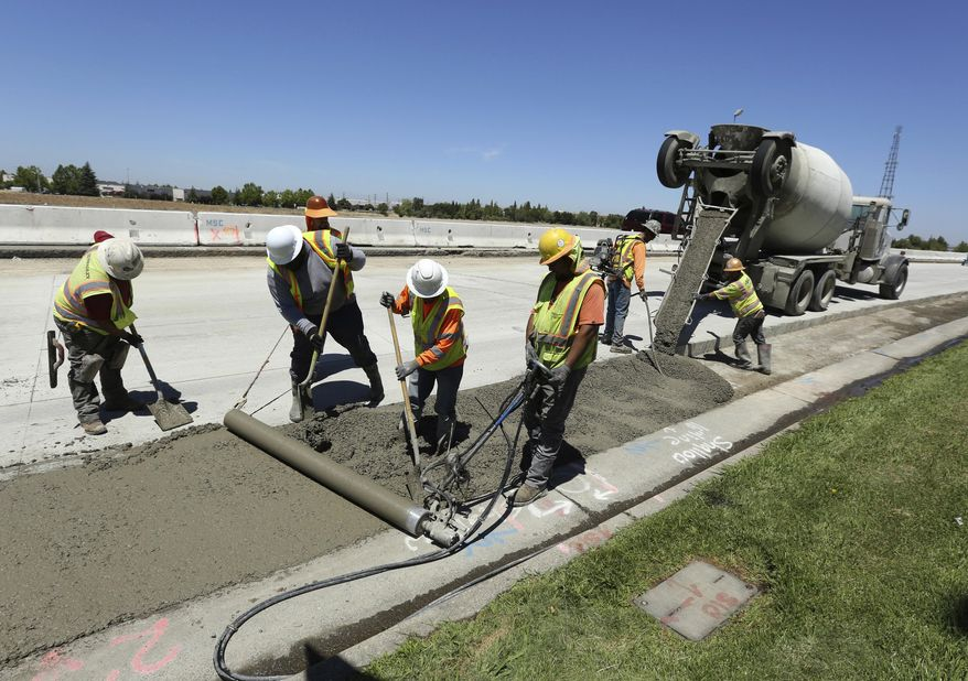 In this July 11, 2018, file photo, workers repave a street in Roseville, Calif., partially funded by a gas tax hike passed by the Legislature in 2017. Republican officeholders have plowed money into a November ballot initiative campaign to repeal the tax increase. (AP Photo/Rich Pedroncelli) ** FILE **