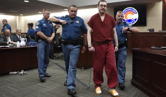 FILE - In this Aug. 26, 2015, file photo, Colorado theater shooter James Holmes, right, is led out of the courtroom after being formally sentenced in Centennial, Colo., to serve life in prison without parole. Holmes was convicted of killing 12 people and injuring 70 in the attack. In a new book and an interview with The Associated Press, psychiatrist William H. Reid, who spent hours talking with Holmes, says what led Holmes to open fire was a vortex of his mental illness, his personality and his circumstances, along with other, unknown factors. (RJ Sangosti/The Denver Post via AP, Pool, File)