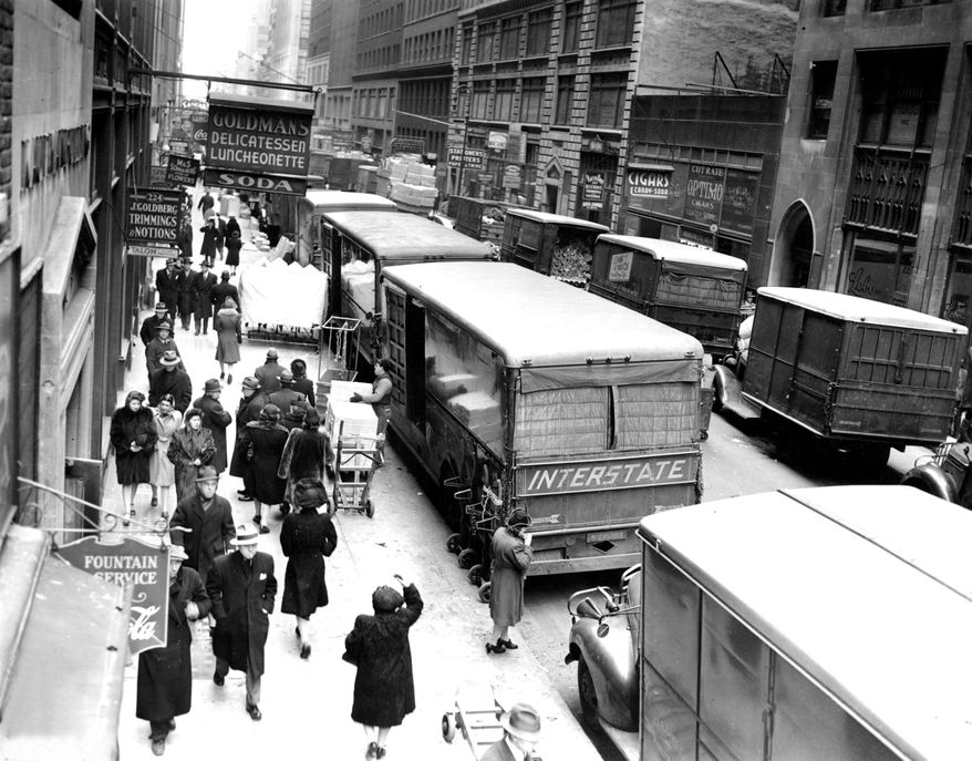 FILE - In this Nov. 29, 1943, file photo, people walk down on a street in New York's Garment District between Broadway and Eighth Avenue.  Hundreds of thousands of garment workers once toiled in the sweaty, elbow-to-elbow workshops of midtown Manhattan before the whirring of sewing machines was mostly silenced by foreign competition. But a group of New Yorkers - manufacturers, landlords, designers, politicians - want to preserve some of the bustling sewing scene by zoning the neighborhood for at least 300,000 square feet of garment workshops now serving higher-end designers. (AP Photo/File)