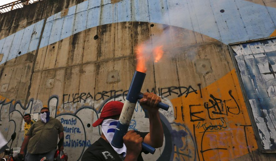FILE - In this July 26, 2018 file photo, a demonstrator fires a home made mortar while others gather to commemorate 100 days of anti-government protests demanding the resignation of President Daniel Ortega and the release of all political prisoners, in Managua, Nicaragua. The rights group, Nicaraguan Pro-Human Rights Association, which has documented killings during months of political unrest, says it is closing its offices due to threats and harassment. (AP Photo/Alfredo Zuniga, File)