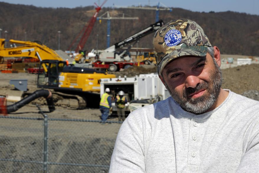 In this April 30, 2018 photo, Chip Kohser, the Beaver county Republican chairman, stands overlooking the construction of a chemical plant on the banks of the Ohio River near Beaver, Pa., that will help convert natural gas into plastic, creating hundreds of jobs in an area that has seen population dwindle since the collapse in the 1980's of the steel industry. (AP Photo/Gene J. Puskar)