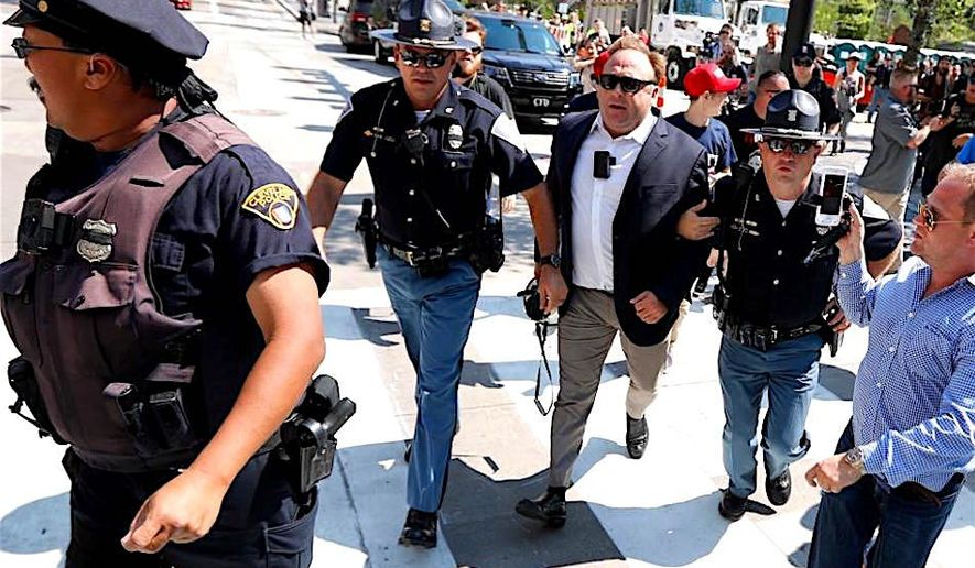 Alex Jones, in the center of a police escort in Cleveland, Ohio, has produced content which raised the ire of major social media providers. (Associated Press)