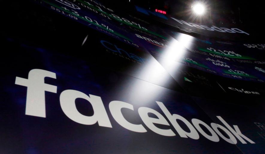 FILE- In this March 29, 2018, file photo, the logo for Facebook appears on screens at the Nasdaq MarketSite in New York's Times Square. Facebook reports earnings Wednesday, April 25. (AP Photo/Richard Drew, File)