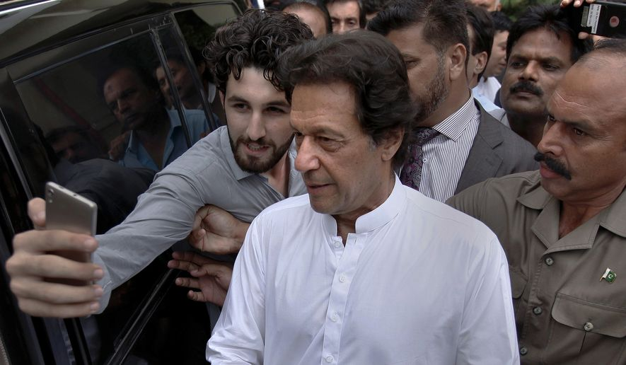 A Pakistani takes selfie with Imran Khan, center, head of the Pakistan Tehreek-e-Insaf party, as he leaves a party meeting in Islamabad, Pakistan, Monday, Aug. 6, 2018. The party won the most parliament seats in last month's general elections and is expected to form a governing coalition later this month. (AP Photo/Anjum Naveed) **FILE**