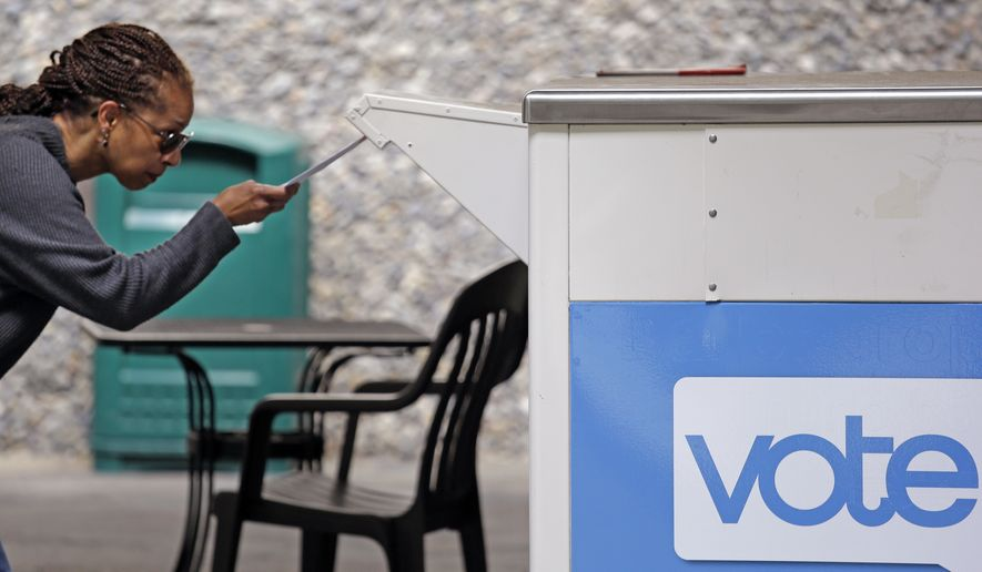FILE - In this Tuesday, Aug. 2, 2018, file photo Eudora Carter inserts her ballot into a drop-off voting box in Seattle. Washington voters will decide which candidates advance to the November ballot in 10 congressional races, a U.S. Senate seat and dozens of legislative contests in the state's primary election. (AP Photo/Elaine Thompson,File)