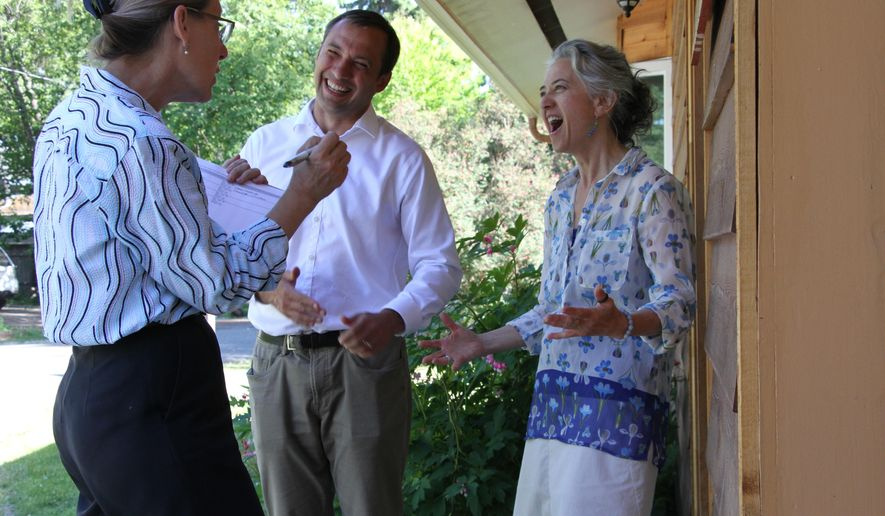 This July 5, 2018, photo shows Alaska Democratic U.S. House candidate Dimitri Shein, middle, and his campaign chair Julie Olson, left, speaking to supporter Dana Dardis while campaigning door-to-door in Anchorage, Alaska. Shein faces several candidates in the Alaska Primary on Aug. 21, 2018, including independent Alyse Galvin. (AP Photo/Mark Thiessen)