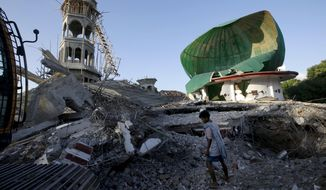 A resident inspects a mosque damaged by an earthquake in North Lombok, Indonesia, Tuesday, Aug. 7, 2018. Thousands left homeless by the powerful quake that ruptured roads and flattened buildings on the Indonesian tourist island of Lombok sheltered Monday night in makeshift tents as authorities said rescuers hadn't yet reached all devastated areas. (AP Photo/Tatan Syuflana)