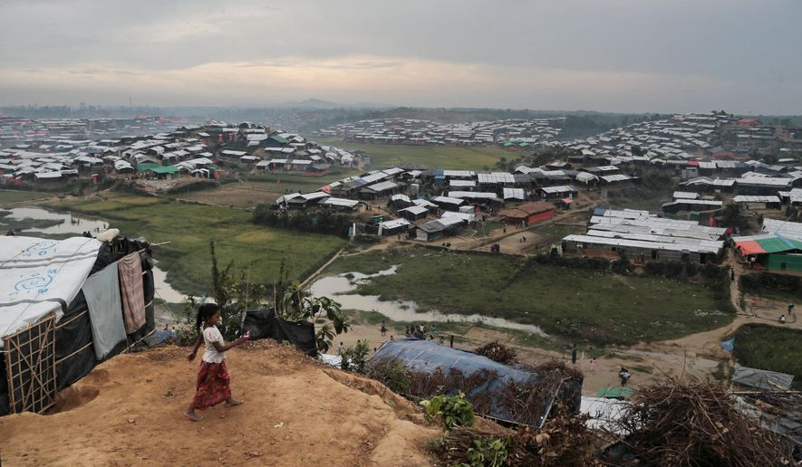 FILE- In this Nov. 17, 2017, file photo, a Rohingya Muslim child who crossed over from Myanmar into Bangladesh, plays in front of her makeshift tent at Jamtoli refugee camp in Ukhiya, Bangladesh. The human rights group Human Rights Watch is calling on Bangladesh's government to abandon controversial plans to relocate Rohingya refugees to a small, uninhabited island said to be at severe risk of serious flooding. (AP Photo/A.M. Ahad, File)