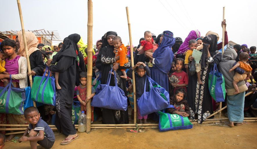FILE - In this Jan. 15, 2018, file photo, Rohingya Muslim women with their children stand in a queue outside a food distribution center at Balukhali refugee camp 50 kilometers (32 miles) from, Cox's Bazar, Bangladesh. The human rights group Human Rights Watch is calling on Bangladesh's government to abandon controversial plans to relocate Rohingya refugees to a small, uninhabited island said to be at severe risk of serious flooding. (AP Photo/Manish Swarup, File)