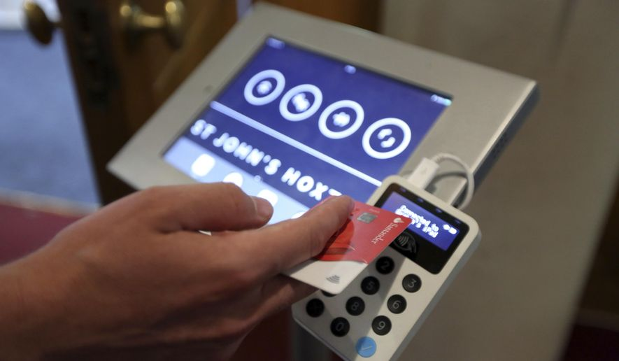 In this photo taken on Thursday Aug. 2, 2018, Aaron Rodewald, an operations and finance manager at St. John's Church, demonstrates a device that allows churchgoers to donate money using contactless payments, in Hoxton, London. Thousands of Christian churches across the world are now using portable card readers or apps to take donations as people increasingly stop carrying cash on them. The Church of England says 16,000 religious sites now have access to portable card readers. In the U.S., hundreds of churches have installed kiosks where the faithful can swipe a card to donate. (AP Photo/Robert Stevens)