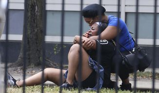 In this Sunday, Aug. 5, 2018 photo, two women cry outside the Stroger Hospital in Chicago after they were asked to leave due to overwhelming crowds of family and friends of shooting victims. Police Superintendent Eddie Johnson plans to discuss the weekend violence during a Monday news conference. (Antonio Perez/Chicago Tribune via AP)