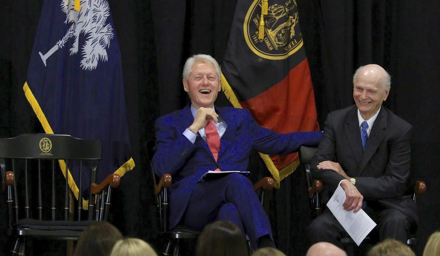 Former President Bill Clinton, left, and former South Carolina Gov. Richard Riley laugh at an event at University South Carolina Monday, Aug. 6, 2018, in Columbia, S.C. The former president spoke to attendees at a reception to officially open Riley's special collections. Clinton tapped Riley to serve as his secretary of Education, a post he held for all eight years of Clinton's administration. (Tim Dominick/The State via AP)