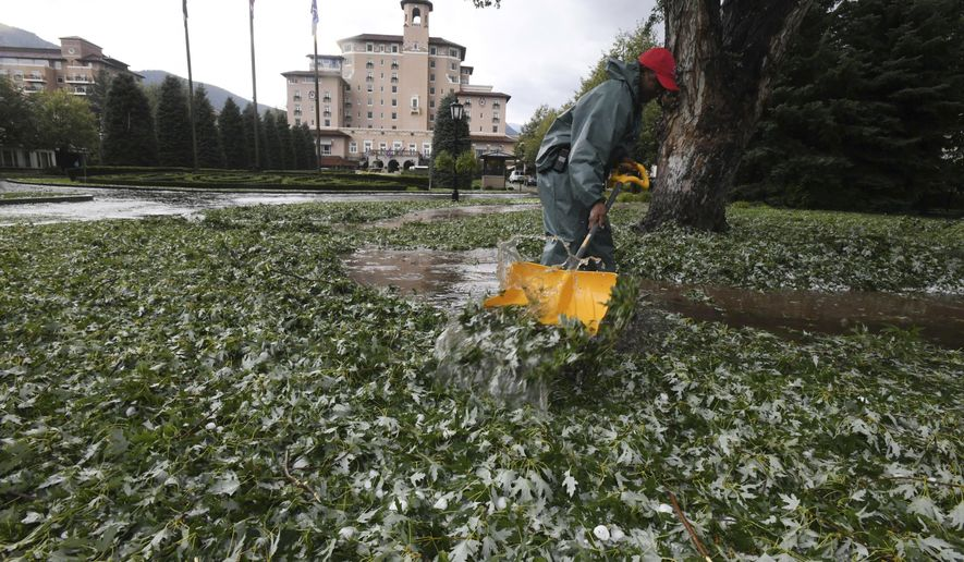 The Broadmoor Hotel employee Carlton Burton shovels leaves and hail after a storm Monday, Aug. 6, 2018, damaged trees, vehicles and buildings in the Colorado Springs, Colo., area. (Jerilee Bennett/The Gazette via AP)