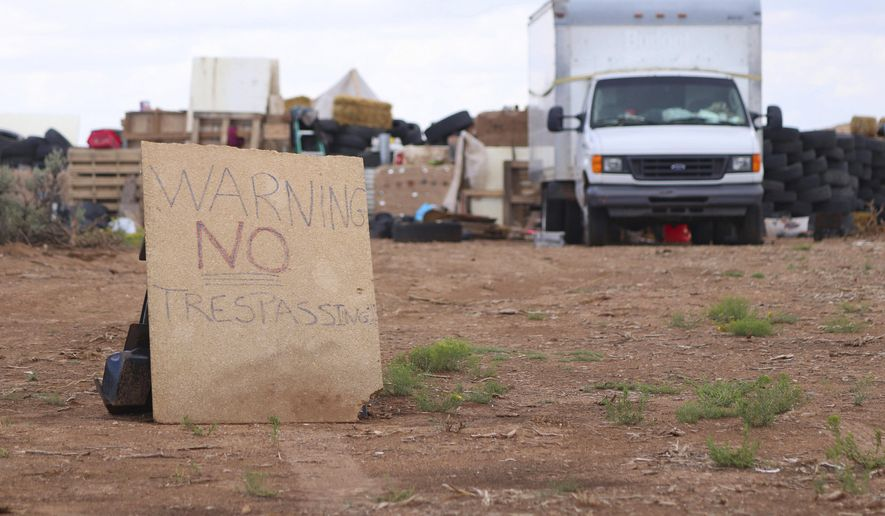 """This Aug. 5, 2018, photo shows a """"no trespassing"""" sign outside the location where people camped near Amalia, N.M. Three women believed to be the mothers of 11 children found hungry and living in a filthy makeshift compound in rural northern New Mexico have been arrested, following the weekend arrests of two men, authorities said Monday, Aug. 6. (Jesse Moya/Santa Fe New Mexican via AP)"""