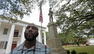 In this Wednesday, Aug. 1, 2018 photo, Ronnie Anderson, an African-American man charged with possession of a firearm by a convicted felon, poses for a photo in front of a confederate statue on the lawn of the East Feliciana Parish Courthouse, where he is facing the charge, in Clinton, La. The statue of the unnamed Confederate soldier has stood since 1909 in front of the courthouse in East Feliciana Parish, hands resting on his rifle looking down on the flow of lawyers, jurors and defendants going into the white columned building. (AP Photo/Gerald Herbert)
