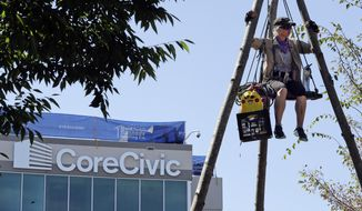 Julie Henry sits on a suspended platform as she protests outside the headquarters of CoreCivic Monday, Aug. 6, 2018, in Nashville, Tenn. The Tennessee-based company is one of the nation's largest private prison operators and also runs eight immigration detention centers for Immigration and Customs Enforcement. (AP Photo/Mark Humphrey)