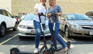 FILE - In this Wednesday, July 11, 2018 file photo, Kirby Bridges, left, and Megan Garlington pose with the Bird scooters they were taking for an afternoon ride in Milwaukee. Bird Rides Inc. has removed its electric scooters from the streets of Milwaukee in an agreement with the city to bring them back once there's a regulatory framework in place. The deal announced Monday Aug. 6, 2018 comes after a weeks-long dispute between Milwaukee officials and the California-based company over whether the scooters are legal to be on city streets. (AP Photo/Ivan Moreno, File)
