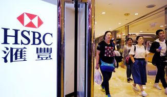 FILE - In this Feb. 20, 2018, file photo, people walk past an HSBC local branch in Hong Kong. Global bank HSBC says its pre-tax profit in the first half of the year rose 4.6 percent as its strategy focused on growing markets paid off. The London-based bank $10.7 billion pre-tax profit in January-June compared with $10.2 billion a year earlier. (AP Photo/Vincent Yu, File)