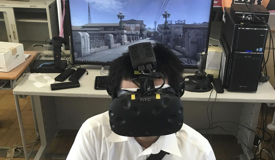 In Friday, Aug. 8, 2018, photo, Namio Matsura, 17-year-old member of the computation skill research club at Fukuyama Technical High School, watches Hiroshima city before atomic bomb fell in virtual reality experience at the high school in Hiroshima, western Japan. Although it's impossible to relive a moment in history, a group of the students have recreated the moment an atomic bomb dropped over the city through VR to portray the livelihood of people that was taken away as a result of the bombing. (AP Photo/Haruka Nuga)