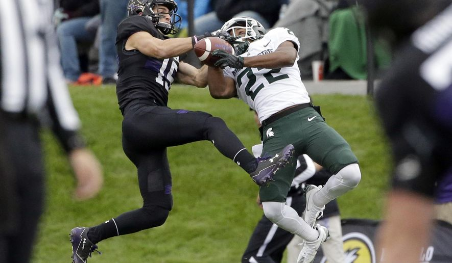 FILE - In this Saturday, Oct. 28, 2017, file photo, Northwestern wide receiver Macan Wilson, left, and Michigan State cornerback Josiah Scott battle for the ball during the first half of an NCAA college football game in Evanston, Ill. Michigan State coach Mark Dantonio announced Monday, Aug. 6, 2018, that cornerback Josiah Scott is expected to miss about two months after a non-contact injury. (AP Photo/Nam Y. Huh, File)
