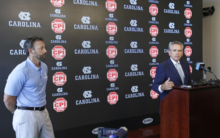 North Carolina coach Larry Fedora, left, listens as athletic director Bubba Cunningham makes comments during the NCAA college football team's media day in Chapel Hill, N.C., Monday, Aug. 6, 2018. Thirteen North Carolina football players face suspensions for selling team-issued shoes, a secondary NCAA violation. (AP Photo/Gerry Broome)
