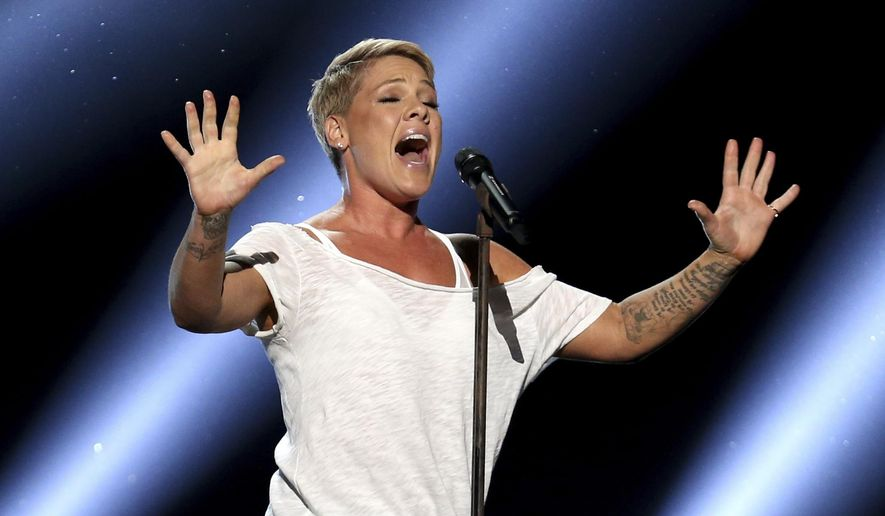 """FILE - In this Jan. 28, 2018, file photo, Pink performs """"Wild Hearts Can't Be Broken"""" at the 60th annual Grammy Awards at Madison Square Garden in New York.  Pink was admitted to a Sydney hospital on Monday, Aug. 6, with a virus, forcing her to postpone a second show, her promoter said. The singer's """"Beautiful Trauma"""" world tour's first concert in Sydney was scheduled for last Friday, but she canceled that show on doctor's orders. She battled through a Saturday night show. (Photo by Matt Sayles/Invision/AP, File)"""