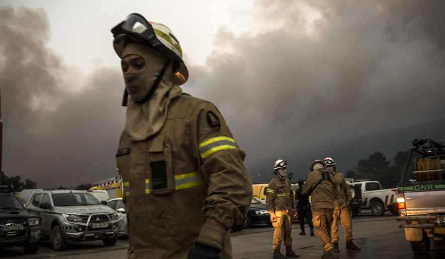 A firefighter group set before heading towards the fire at the village of Monchique, in southern Portugal's Algarve region, Sunday, Aug. 5 2018. Over 700 firefighters were still battling a forest fire near the Portuguese town of Monchique in the southern Algarve region, a popular tourist destination. (AP Photo/Javier Fergo)