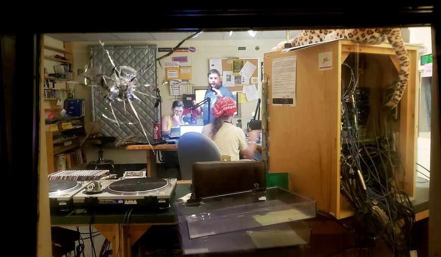 A bullet hole is seen in a studio window at community radio station WORT-FM in Madison, Wis., after an early morning shooting by an intruder left one of the station's disc jockeys with non-life threatening injuries Sunday, Aug. 5, 2018. (Logan Wroge/Wisconsin State Journal via AP)