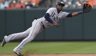 Tampa Bay Rays shortstop Adelny Hechavarria stops a ground ball hit by Mark Trumbo in the eighth inning of a baseball game, Sunday, July 29, 2018, in Baltimore. Trumbo earned a single on the play. (AP Photo/Gail Burton)