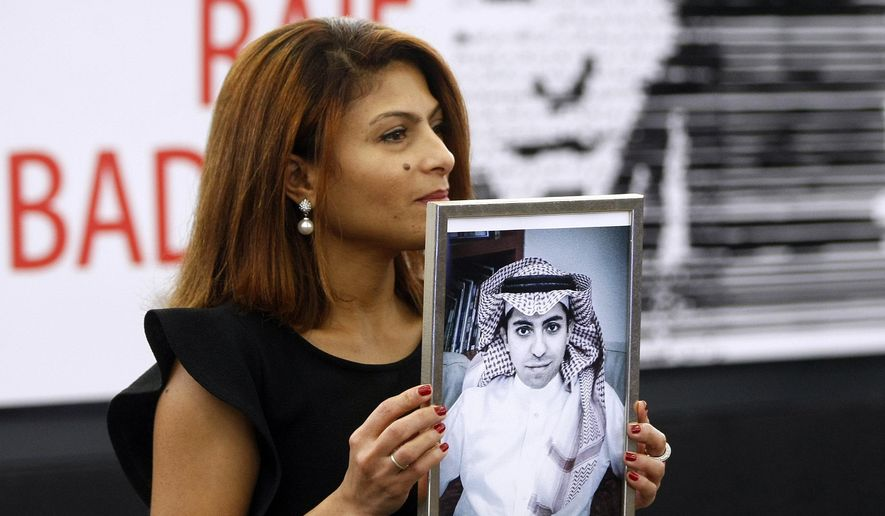 In this Dec, 16, 2015 file photo, Ensaf Haidar, wife of the jailed Saudi Arabian blogger Raif Badawi, shows a portrait of her husband as he is awarded the Sakharov Prize, in Strasbourg, France. Saudi Arabia has given Canada's ambassador 24 hours to leave the kingdom after Canada criticized the recent arrest of women's rights activists. Among the arrested activists is Samar Badawi, whose writer brother Raif Badawi was arrested in Saudi Arabia in 2012 and later sentenced to 1,000 lashes and 10 years in prison for insulting Islam while blogging. (AP Photo/Christian Lutz, File)