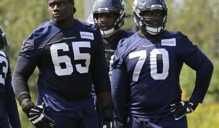 Seattle Seahawks offensive guard Germain Ifedi (65) stands on the field next to offensive guard Rees Odhiambo (70) during NFL football training camp, Monday, Aug. 6, 2018, in Renton, Wash. (AP Photo/Ted S. Warren)