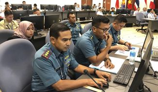 FILE - In this Friday, Aug. 3, 2018, file photo, Indonesian Navy staff participate in a computer-simulated drill in Singapore. Chinese and Southeast Asian naval forces have staged their first computer-simulated drills so they can jointly respond to emergencies and build trust amid the long-seething disputes in the South China Sea. (AP Photo/Jim Gomez, File)