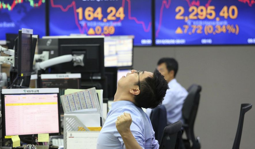 A currency trader stretches himself while working at the foreign exchange dealing room of the KEB Hana Bank headquarters in Seoul, South Korea, Monday, Aug. 6, 2018. Asian stocks rose Monday despite a new Chinese threat of tariff hikes on U.S. goods after Washington reported solid employment numbers. (AP Photo/Ahn Young-joon)