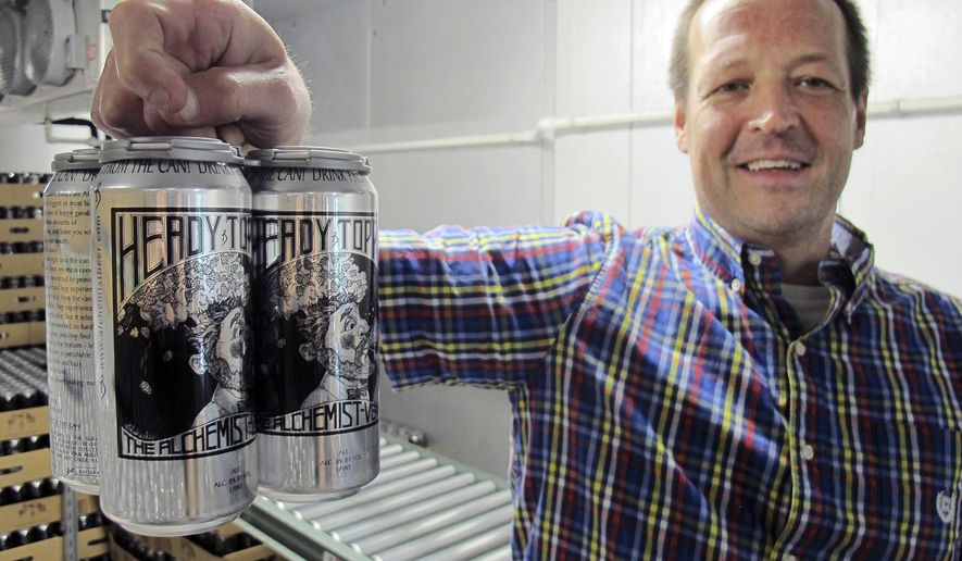 In this Aug. 1, 2018 photo, retail manager Jay Meeks holds a four-pack of Heddy Topper at The Alchemist brewery in Stowe, Vt. The woods of northern New England are luring beer tourists. No discussion of beer in Vermont is complete without The Alchemist, a family run brewery that specializes in fresh, unfiltered IPA. (AP Photo/Wilson Ring)