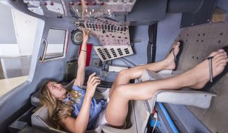 In this July 12, 2018 photo, Tara Clemenceau, 11, visiting from France, tries her hand at the controls of a Mercury space capsule at the U.S. Space & Rocket Center in Huntsville, Ala. Huntsville's tourism industry is rooted in the U.S. space program and its critical, ongoing research into getting astronauts back to the moon and on to Mars. (AP Photo/Vasha Hunt)