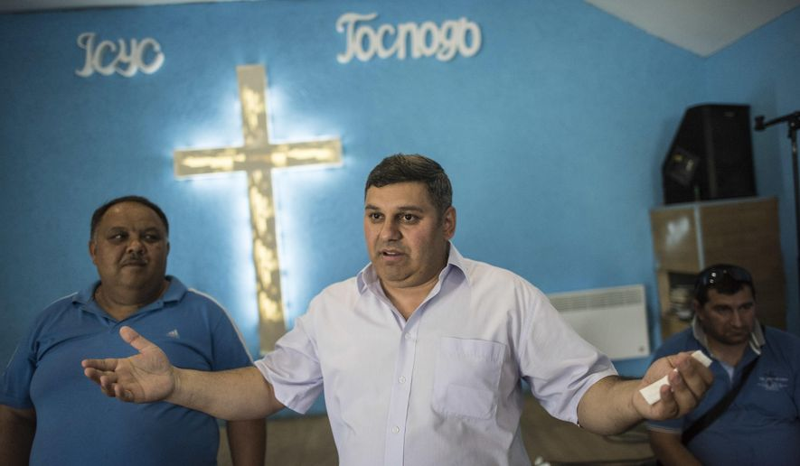 In this photo taken on Monday, June 4, 2018 and provided by OSCE Project Co-ordinator in Ukraine Press Service, Roma activist Myroslav Horvat of the World Roma Organization, center, gestures while speaking to journalists in a church inside a Roma encampment on the outskirts of Uzhhorod, western Ukraine. After attackers charged into a Roma encampment on the outskirts of Kiev, a leader of an ultranationalist group posted photos of his colleagues clearing the site and burning tents left behind. The April attack was the first of 11 forced removals that civilians in Ukraine carried out at Roma settlements an ethnic group, also known as Gypsies, that faces discrimination and disdain in much of Europe. (Evgeniy Malolletka,OSCE Project Co-ordinator Press Service via AP)