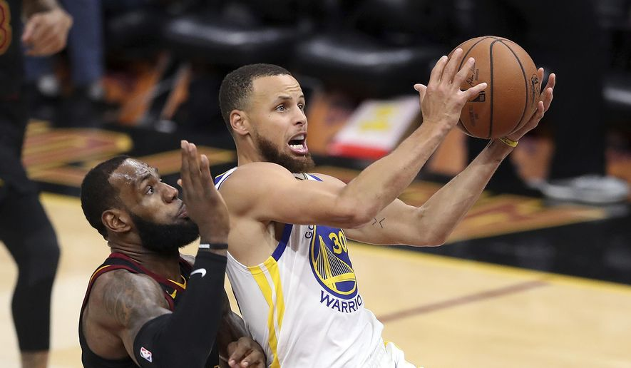 FILE - In this June 6, 2018 file photo, Golden State Warriors' Stephen Curry goes to the basket against Cleveland Cavaliers' LeBron James, left, during the second half of Game 3 of basketball's NBA Finals in Cleveland. Curry can only imagine the intensity level of the Lakers-Warriors rivalry now that LeBron James has landed in L.A. After four straight NBA Finals against James and the Cleveland Cavaliers, two-time defending champion Golden State will get four matchups against James during the regular season. (AP Photo/Carlos Osorio, File) **FILE**