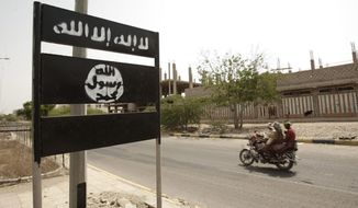 """FILE - In this Friday, June 15, 2012 file photo, an al-Qaida logo is seen on a street sign in the town of Jaar in southern Abyan province, Yemen. Arabic on the logo reads, """"There is no god but God,"""" and """"Muhammad is the messenger of God."""" Jaar was one of several southern towns that al-Qaida in the Arabian Peninsula took over in 2011 and ruled until the following year when it was driven out by a government offensive that wreaked widespread damage. It was just one phase in the continual back and forth of expansions by the group and crack-downs. (AP Photo/Hani Mohammed, File)"""