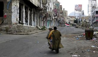 Men ride through streets wrecked by fighting in Taiz, Yemen in this Feb. 4, 2018, photo. The city gives the clearest example of the intertwining of al-Qaida with militias funded by the U.S.-backed coalition to fight the Houthi rebels. Al-Qaida militants are among the fiercest fighters in the city, driving the rebels out of some areas, and militia commanders have close ties to and recruit from the group. (AP Photo)
