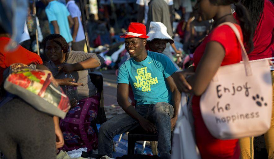 Zimbabweans shop for clothes at the clothing market in Bulawayo, Zimbabwe, Sunday, Aug. 5, 2018. (AP Photo/Jerome Delay)
