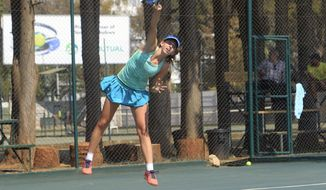 Victoria Sasinka, 13, of the US serves the ball, during an International Tennis Federation Tournament, at Harare Sports Club, in Harare, Monday, Aug. 6, 2018. As Zimbabwean soldiers opened fire on rioters, protesters and bystanders after a disputed election, teen-agers in an International Tennis Federation tournament were battling each other on hard courts a few kilometers (miles) from the deadly violence. (AP Photo/Tsvangirayi Mukwazhi)