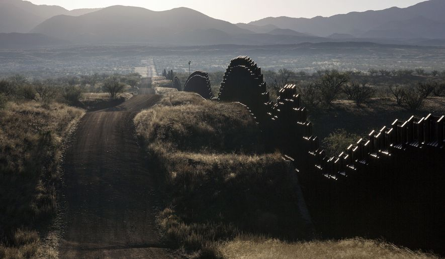 FILE - This April 2, 2017 file drone photo shows the U.S.-Mexico border fence on the outskirts of Nogales in southern Arizona. A U.S. border patrol agent is going on trial for second-degree murder in U.S. District Court in Tucson on Tuesday, March 20, 2018, in a rare Justice Department prosecution of a fatal cross-border Mexico shooting. (AP Photo/Brian Skoloff, File)