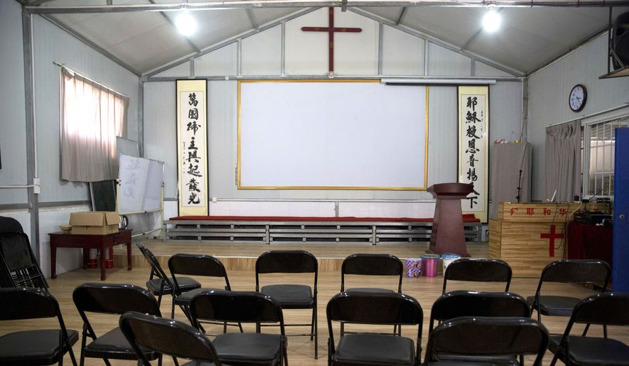 "Chinese calligraphy which reads ""All nations belong to the Lord arising to shine"" at left and ""Jesus's salvation spreads to the whole world"" at right are displayed below a crucifix in a house church shut down by authorities near the city of Nanyang in central China's Henan province. (Associated Press)"