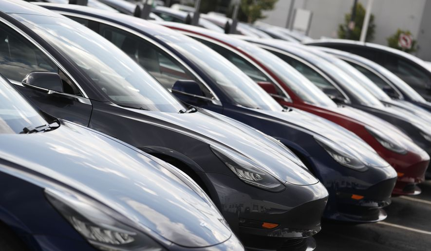 In this Sunday, July 8, 2018, photograph, 2018 Model 3 sedans sit on display outside a Tesla showroom in Littleton, Colo. (AP Photo/David Zalubowski) ** FILE **