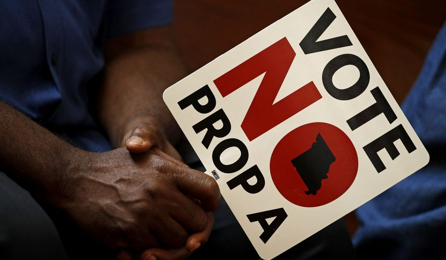 People opposing Proposition A listen to a speaker during a rally in Kansas City, Mo. Missouri votes Tuesday, Aug. 7 on a so-called right-to-work law, a voter referendum seeking to ban compulsory union fees in all private-sector workplaces. (AP Photo/Charlie Riedel, File)