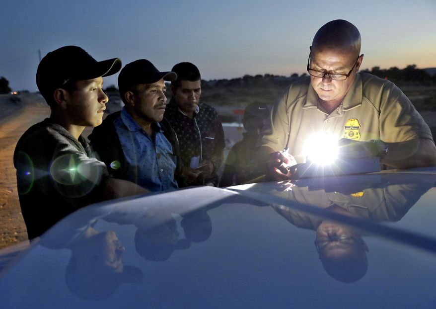 A U.S. Customs and Border Patrol agent gathers information on four Guatemalan nationals, including two men and a pair of 12 and 13-year-old boys, Wednesday, July 18, 2018, in Yuma, Ariz. Thousands of families and unaccompanied children are continuing to cross the U.S. border in Arizona and California even after learning of the government's family separation policy upon apprehension. (AP Photo/Matt York)