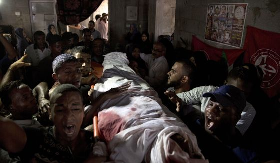Palestinian mourners carry the body of 23 year-old Hamas fighter, Ahmad Morjan, mourn at the family home during his funeral, in the Jabaliya refugee camp, Northern Gaza Strip, Tuesday, Aug. 7, 2018. The Israeli military said it targeted a Hamas military post in northern Gaza after militants opened fire, and Hamas said two of its fighters were killed. (AP Photo/Khalil Hamra)
