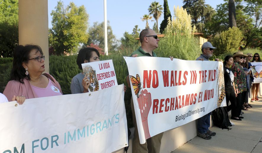 Members of the Center for Biological Diversity and other immigrant advocates protest outside 9th U.S. Circuit Court of Appeals court hearing challenging Trump's border wall Tuesday, Aug. 7, 2018, in Pasadena, Calif. A federal appeals court will hear arguments by the state of California that the Trump administration overreached by waiving environmental reviews to speed construction of the president's prized border wall with Mexico. At issue Tuesday before a three-judge panel in Pasadena, California, is a 2005 law that gave the Homeland Security secretary broad authority to waive dozens of laws including the National Environmental Policy Act and Endangered Species Act. (AP Photo/Ariel Tu)